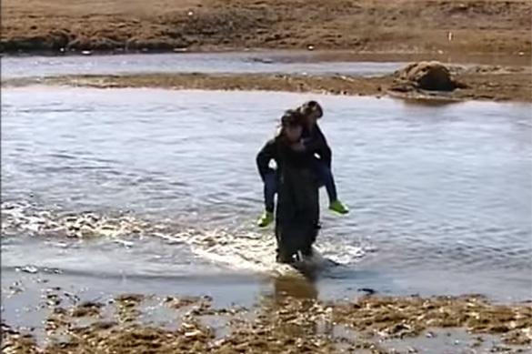 Семиклассник носит первоклашек в школу через реку. ВИДЕО