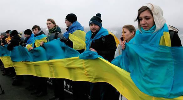 Исключать Украину из СНГ принудительно нельзя - мнение. Люди держат украинский флаг