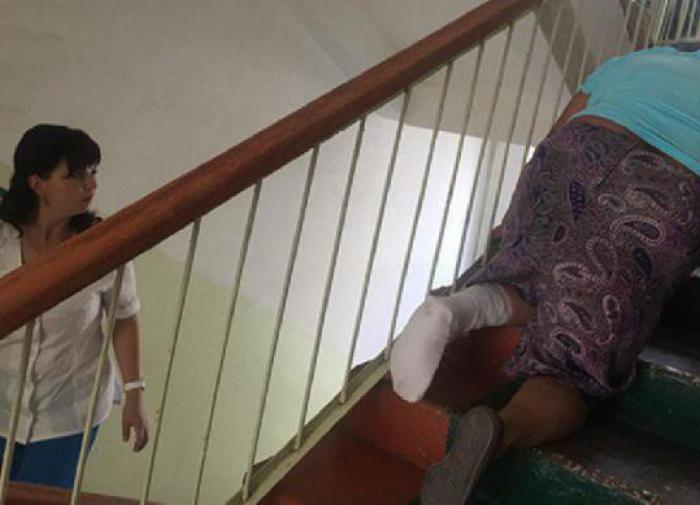 Пожилая женщина ползет по лестнице в поликлинике