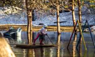 В Новосибирске дети устроили заплыв на плотах на затопленной детской площадке