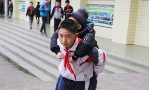 Китайскиий мальчик в течение шести лет носил на руках друга-инвалида в школу