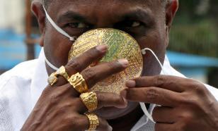 Житель Индии использует защитную маску из чистого золота