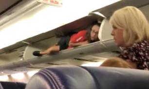 Стюардесса приветствовала пассажиров из полки для ручной клади